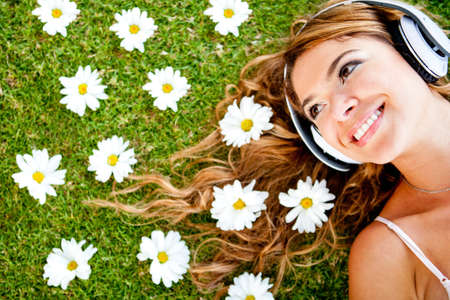 Beautiful woman listening to music with headphones lying outdoors  photo