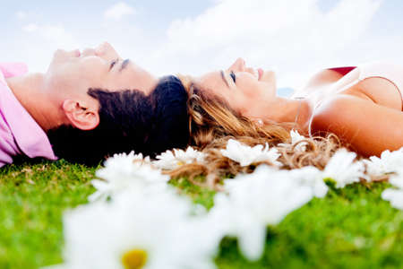 dating couples: Happy loving couple relaxing together lying outdoors