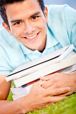 Happy male student with a pile of books  photo