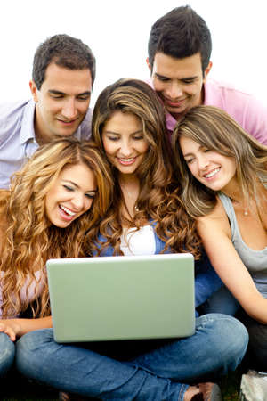Friends social networking on a laptop computer outdoors  photo