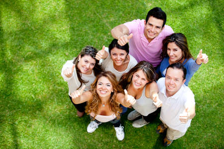 Group of friends smiling with thumbs-up outdoors  photo