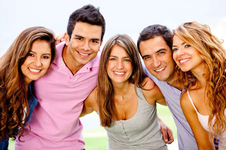 Happy group of friends hugging and smiling outdoors  photo