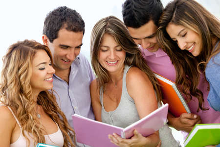 Happy group of young students with a notebook outdoors  Stock Photo - 12393942