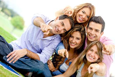 grupo de personas: Grupo de amigos en el parque y sonriente apuntando Foto de archivo
