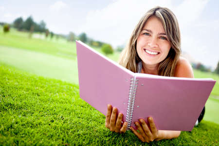 Female student lying at the park with a notebook  photo