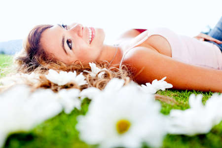 Beautiful woman lying on a garden of flowers and smiling photo