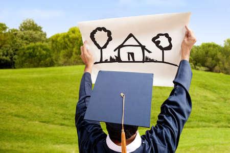 graduacion de universidad: Estudiante de posgrado imaginando el futuro con una casa