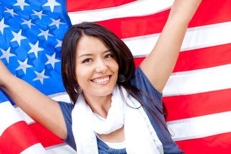 banderas americanas: Mujer orgullosa con la bandera americana y la sonrisa Foto de archivo