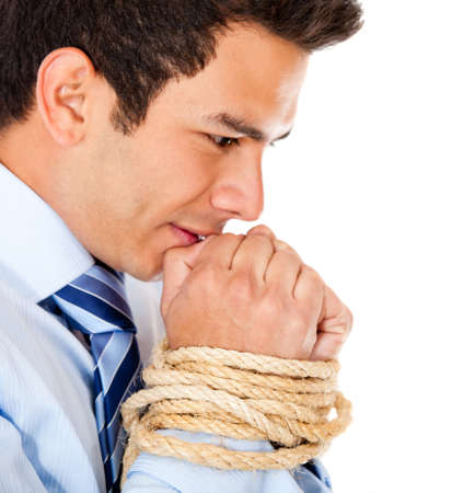 Tortured businessman holding his hands tied with a rope - isolated over white  photo