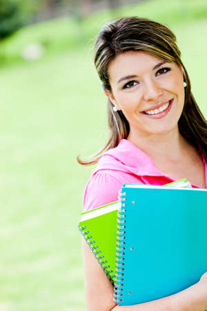 latin students: Beautiful female student outdoors holding notebooks and smiling  Stock Photo