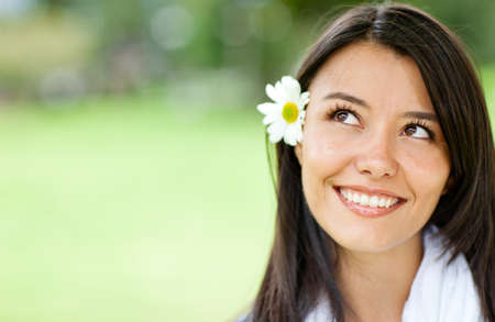 Beautiful thoughtful woman with a flower in her head and smiling  photo