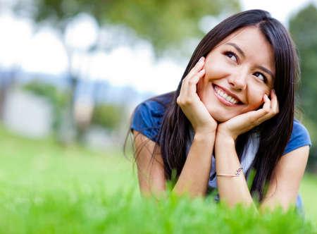ni�a pensando: Hermosa mujer pensativa mirando hacia arriba y sonriendo en el parque Foto de archivo