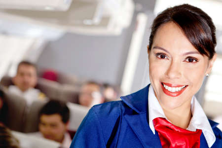 Beautiful air stewardess in an airplane cabin smiling  photo