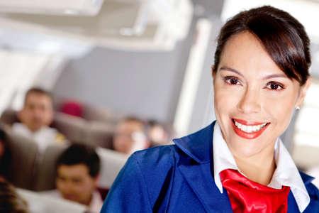 hotesse de l air: Belle h�tesse de l'air dans une cabine d'avion en souriant