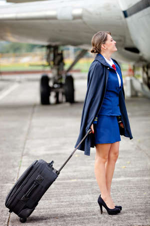 air hostess: Beautiful air hostess with her bag next to an airplane