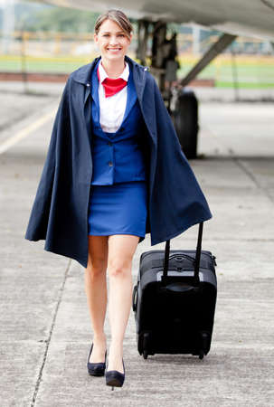 Beautiful air stewardess walking next to an airplane with bag photo