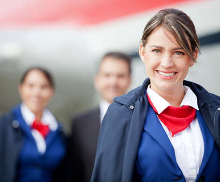Beautiful flight attendant with the cabin crew at the background photo