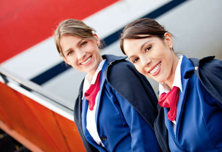 Friendly air hostesses smiling and welcoming into the airplane  photo