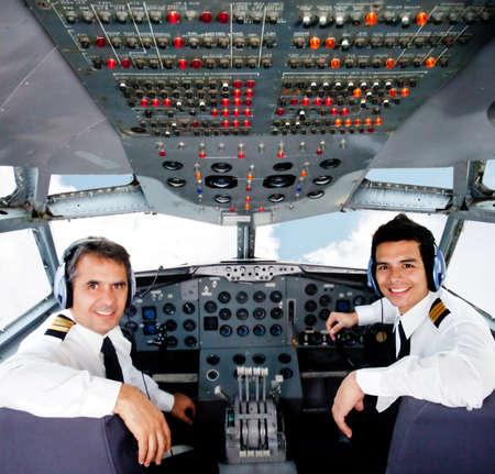 pilotos aviadores: Los pilotos se sientan en una cabina de avi�n que volaba en piloto autom�tico Foto de archivo