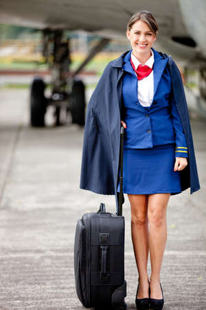 azafata: Auxiliar de vuelo hermosa con su bolso junto a un aiplane