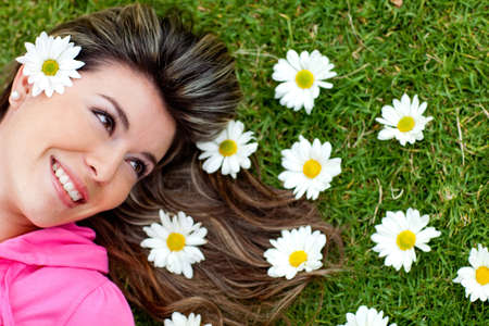 Gorgeous woman portrait lying in a garden of daisies photo