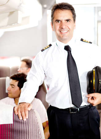 Friendly pilot in the passengers cabin of an airplane smiling  photo