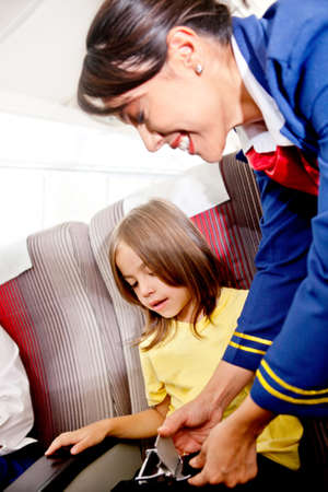 Flight attendant helping a kid to fasten his seatbelt  photo