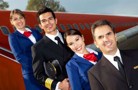 Friendly cabin crew smiling with an airplane at the background photo