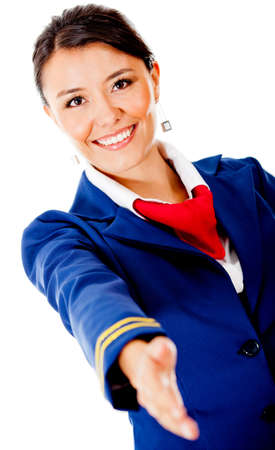 Welcoming air hostess with hand extended – isolated over a white background  photo