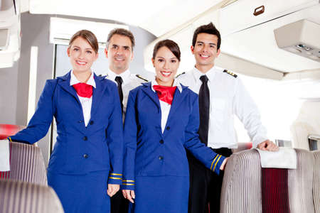 crew: Friendly cabin crew in an airplane smiling