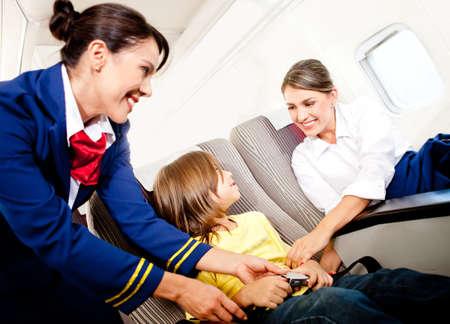 air hostess: H�tesse de l'air aidant un enfant � attacher sa ceinture de s�curit�