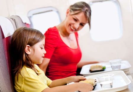 Mother and son having a meal in the airplane while flying  photo