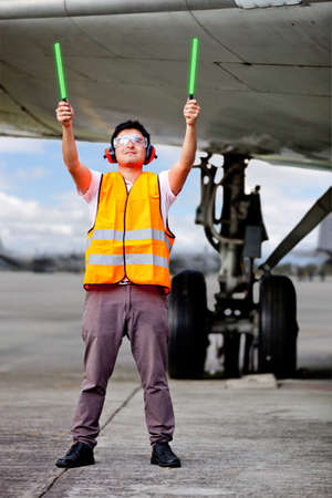 Air traffic controller holding light signs at the airport photo