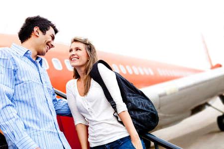 persona viajando: Feliz pareja de enamorados viaja en avi�n y sonriendo