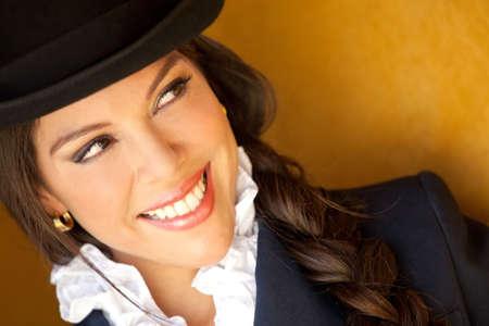 mujer en caballo: Retrato de una bella amazona con un sombrero y sonriente
