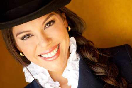 Beautiful horsewoman portrait wearing a hat and smiling  photo