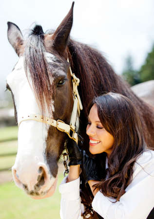 Happy woman with a beautiful horse smiling  photo