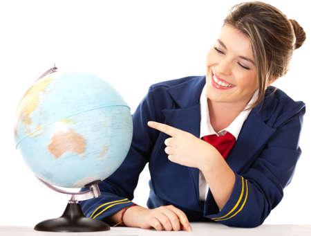 air hostess: H�tesse de l'air pointant vers le monde - isol� sur un fond blanc