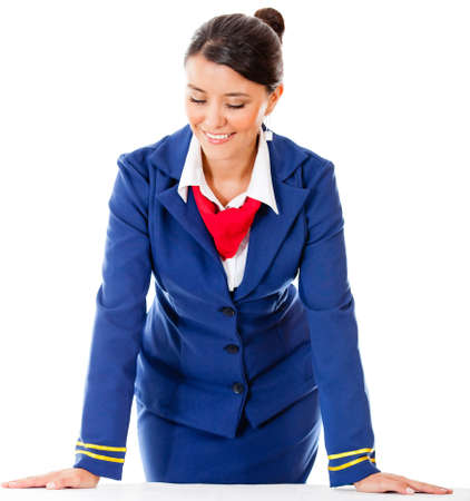 Air hostess leaning on a table - isolated over a white background photo