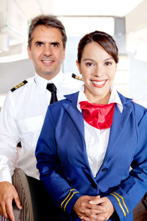 Pilot and air hostess in an airplane cabin smiling photo