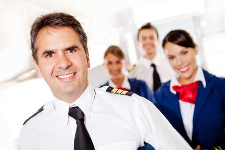 Captain with cabin crew in an airplane smiling  photo