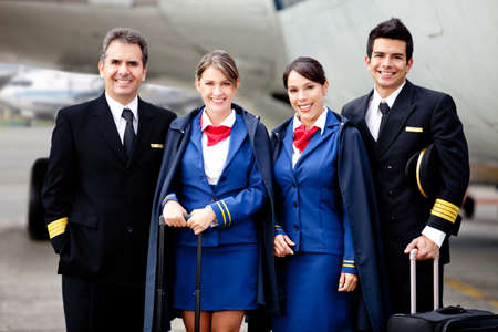 crew: Airplane cabin crew standing at the airport with bags  Stock Photo