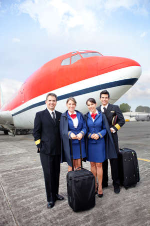 Airplane cabin crew standing at the airport with bags photo