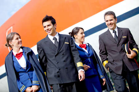 Group of pilots and flight attendants geting off an airplane  photo