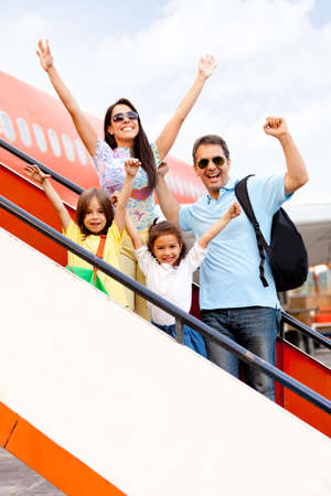 Happy family going on holidays and getting on the airplane  photo