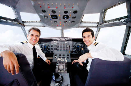 crew: Pilots sitting in an airplane cabin flying and smiling  Stock Photo