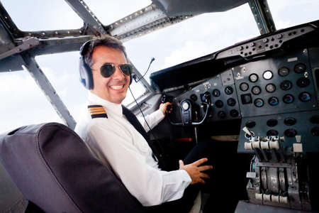 Male pilot sitting in an airplane cabin flying and smiling photo