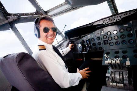pilotos aviadores: Mujer piloto sentado en la cabina del avi�n volando y sonriente