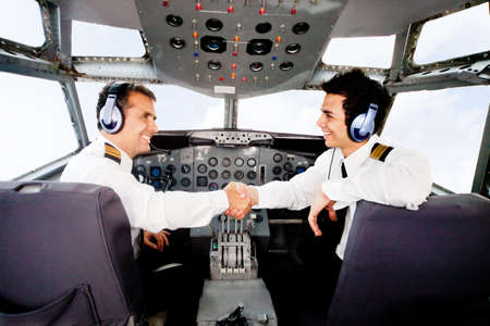 Happy pilots handshaking in the airplane cabin  photo