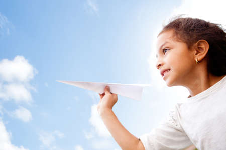 Girl holding a paper airplane and dreaming aboyt flying  photo